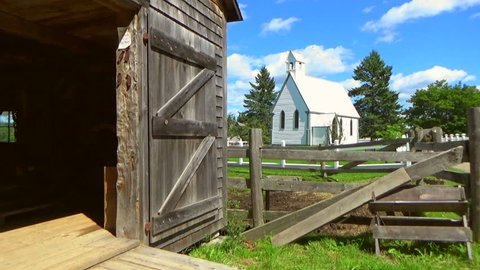 Historic village with farmhouses in Canada. Old Church exterior. Picket fences.