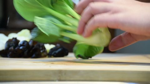 Close-up of professional chef's hands slicing, preparing pak choi, bok choy in half for cooking