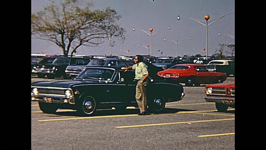 Swansea, United States of America - circa 1970: Old footage of people and vintage cars in the parking lot of Macy's Shop Fashion Clothing and Accessories, on Swansea Mall Drive in 70's.