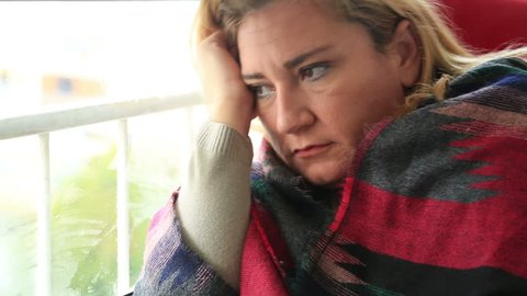 Unhappy middle aged  woman looking the rain falling through a window at home