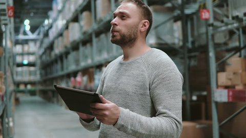 Young man using digital tablet in warehouse, checking goods list at supermarket and looking for items. 4K