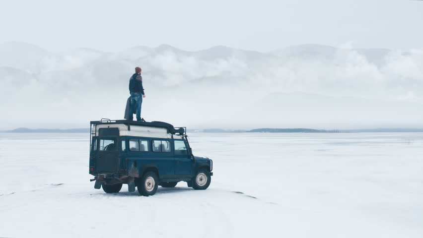 WIDE Caucasian male standing on the roof of old 4x4 off-road vehicle, spreading hands and enjoying the view of mountains over large lake. 4K UHD 60 FPS RAW edited footage