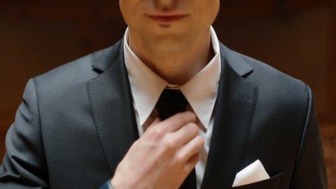 Portrait of young caucasian man in black suit indoor. Model corrects the tie.