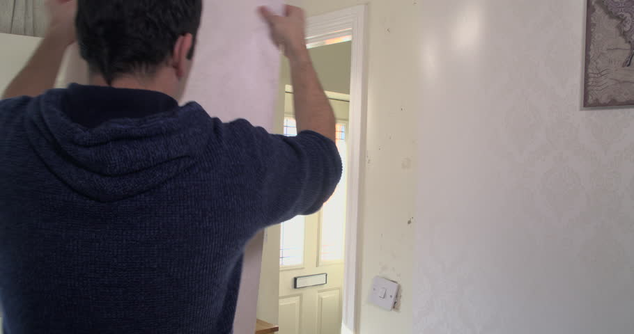 Adult male putting up some new wallpaper in his family home