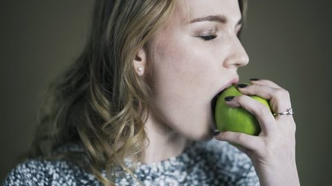 Close up portrait of young woman biting and eating tasty green apple. Locked down real time shot.