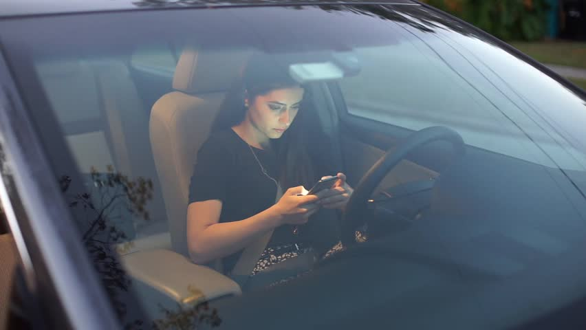 Beautiful girl model sitting in the car and use the phone | Shutterstock HD Video #23902984