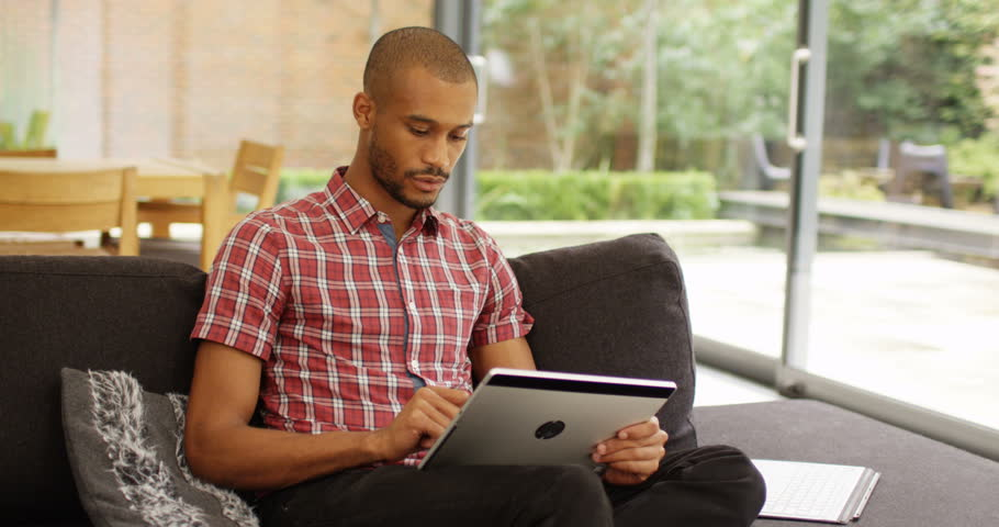 4k, Young African American man using tablet at home.