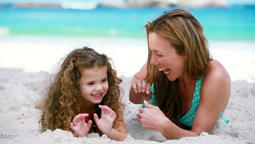 Smiling mother tickling her daughter on the beach