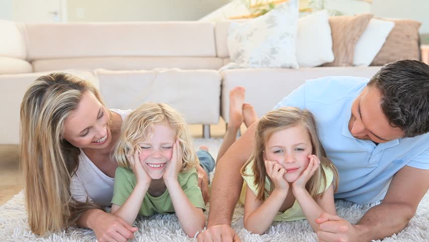 Happy family lying on the floor in the living room