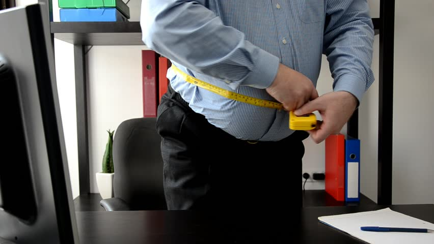 Mature office clerk fails the diet he is on and checks his waist in panic.