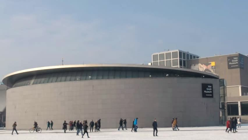 Amsterdam The Netherlands February 2017:  Winter in Amsterdam.  Snow on the Museumplein. Visitors walk through the snow in front of the van Gogh Museum.
