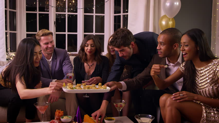 Friends Eating Snacks As They Celebrate At Party Together