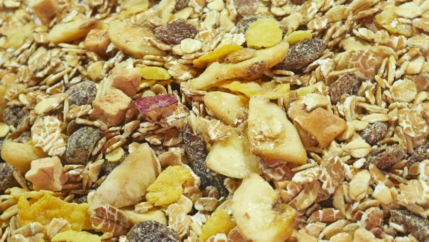 Cereal Muesli or Granola Rotating Closeup with Pieces of Fruits, Nuts, Raisins, Cornflakes and Oatmeal. Healthy breakfast concept