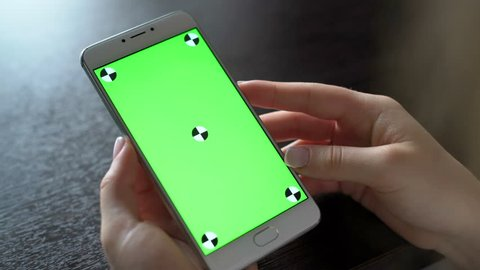 One person use cellular telephone with touch green screen for browsing social networks and communicating closeup. Girl, holding in hand portable gadget close up, as image of tech accessibility concept