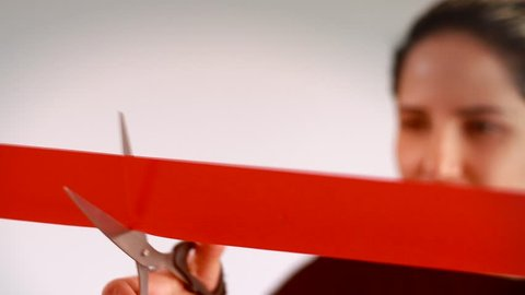 Confidant business woman cutting red ribbon