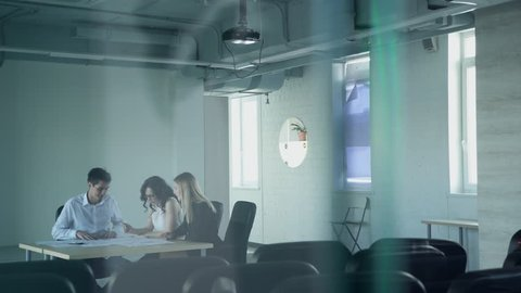 In the empty hall three staff at the table look the paper and talk. Two beautiful young women and a man dressed in office attire sitting behind a desk and discuss important working moments. In the