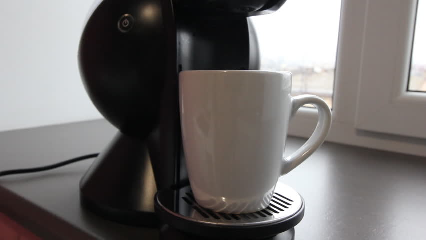 Close up coffee maker machine with white coffee cup. beautiful female hand presses the start button on the panel coffee machine. Coffee machine is broken and gives an error. Button blinks red