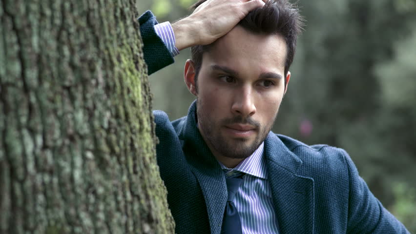 Close up on depresssed business man while holding his head leaning on a tree in a city park #24024604