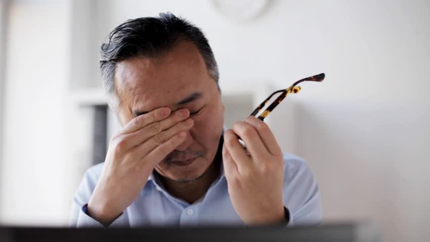 business, overwork, deadline and people concept - tired man in eyeglasses with laptop computer rubbing eyes at office