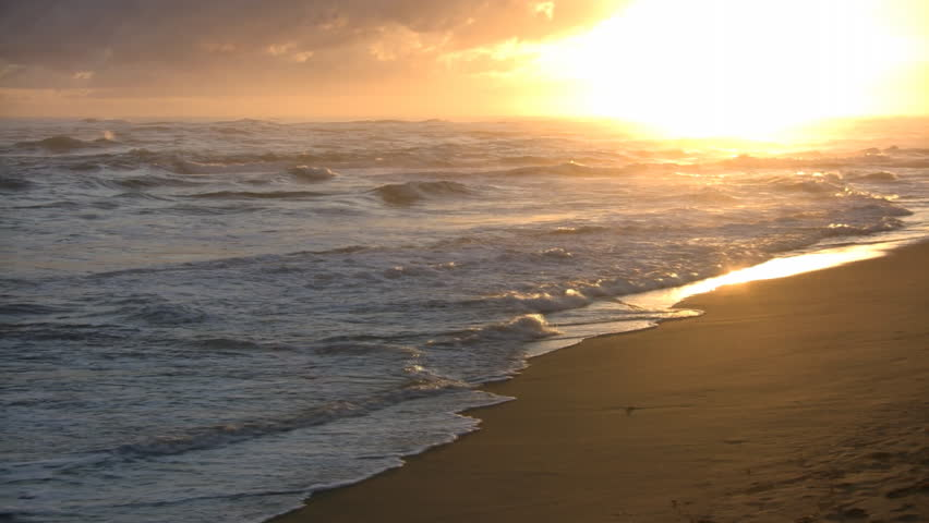 Waves gently wash up onto the beach, then recede as the sun starts to rise. (High Definition)