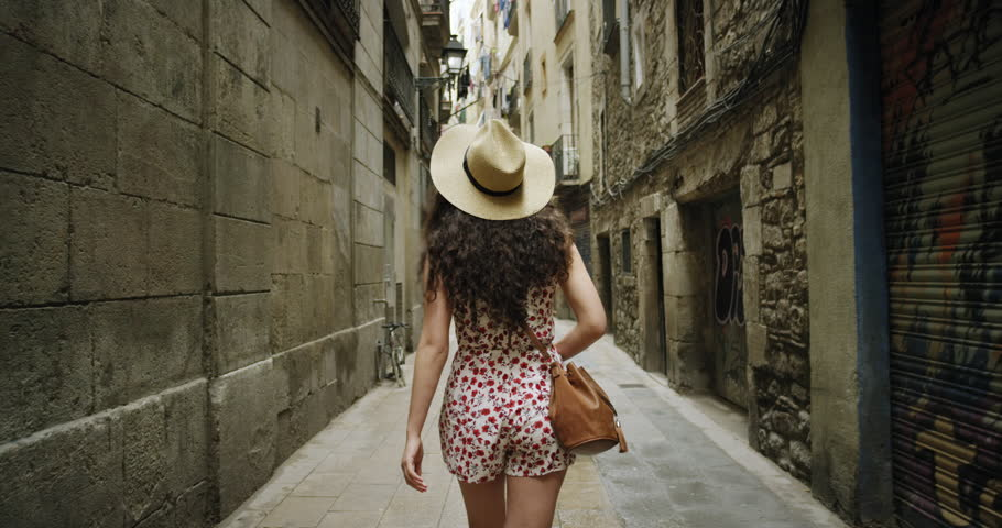 Rear view tourist woman Walking narrow streets of Barcelona Wearing cute summer dress enjoying European summer holiday travel vacation adventure