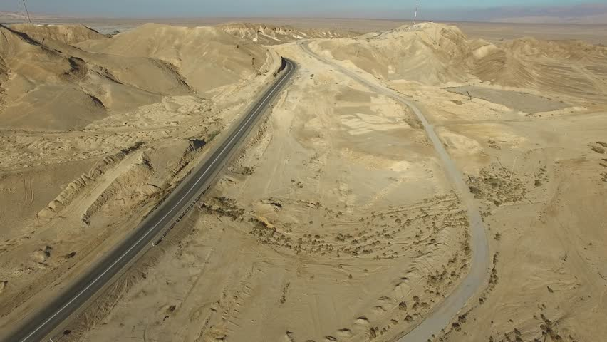 Desert Arava Judean Negev aerial with road in sands and mountains on background