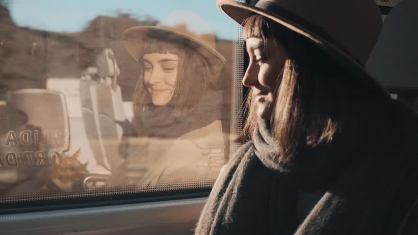 Close up portrait of attractive brunette travels near window in train car and taking photos and videos on her smartphone at sunny winter day
