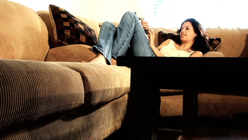 Pretty latino girl relaxes on the sofa with her mobile phone