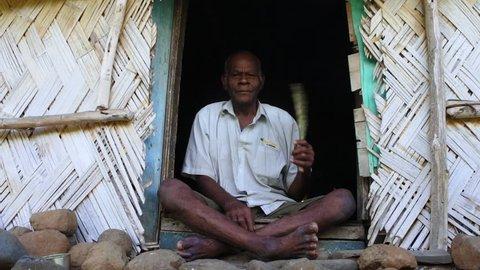 Elderly indigenous Fijian man in his 70's sit outside his village bure home in Navala village in Ba highlands on Viti Levu island, Fiji. Real people, copy space