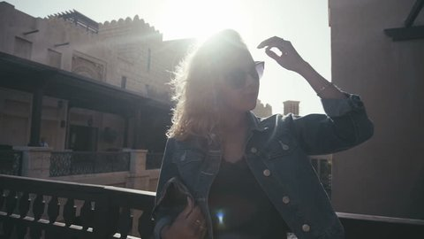 UAE, 2017: Madinat jumeirah. Beautiful young woman in sunglasses standing on the background of the sun and straightens hair. Stylish girl stands on the background of the historical sights of Abu Dhabi