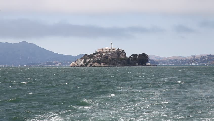 Panoramic boat sea view of Alcatraz island, warden's house and lighthouse of the prison. Bay of San Francisco, United States. Traveling in California. Popular tourist attraction in San Francisco.