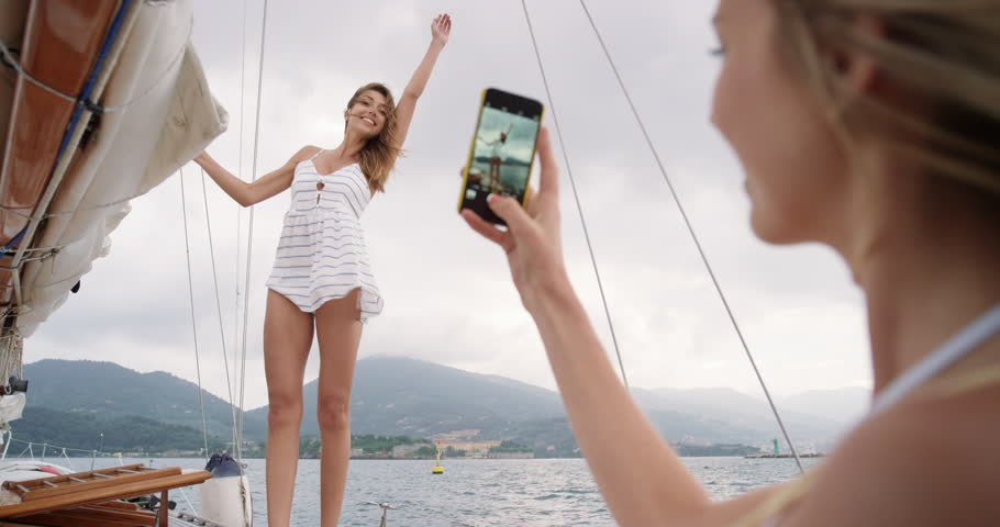 Beautiful woman friends taking photo smart phone social media on sailboat in ocean on luxury lifestyle adventure travel vacation