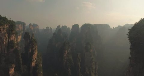 Aerial view of amazing karst pillars at Wulingyuan National Park (Park of Avatar) in Zhangjiajie, Hunan Province, China at sunset. Drone flying over breathtaking scenic area covered with sunset mist.