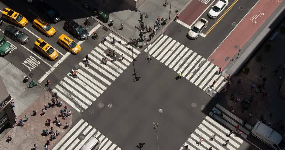 Bird's eye view of a busy intersection in Midtown Manhattan. Looking down on the streets of New York. Yellow taxis, city buses, cars, and people cross through the intersection going to work,timelapse.