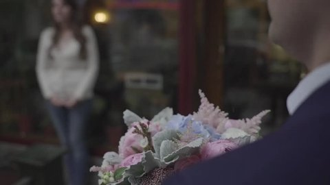 a man gives a girl flowers.