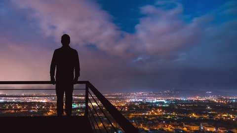 The man stand on the balcony on the background of the night town. Time lapse