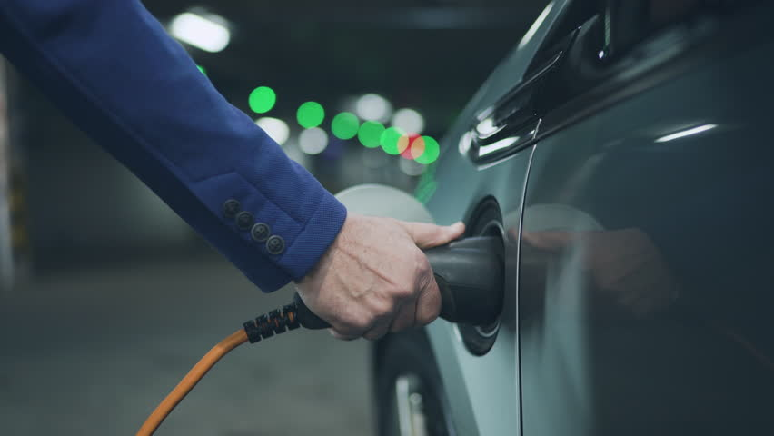 Senior is plugging in power cord to an electric car. Close up. 4K | Shutterstock HD Video #24121744
