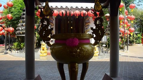 Thai people pray with flower, joss stick and candle at joss stick pot or thurible for praying beautiful chinese goddess Guan Yin bodhisattva statue at Wat Chong Lom in Samutsakorn, Thailand