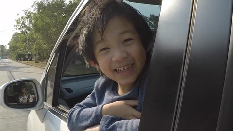 Happy Asian boy travels by car, slow motion