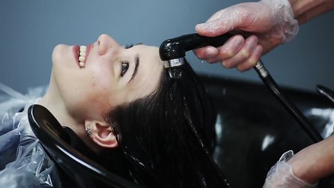 Hairdresser in gloves washing brunette girl hair over sink in beauty shop.