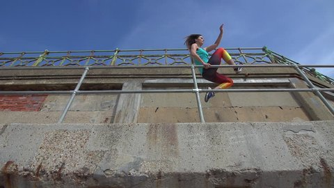 Female Parkour or Free Runner leaps from the underside of a pier.