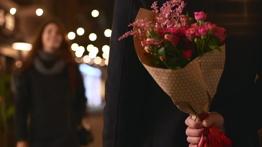 Male in coat hiding behind back bouquet of flowers while Caucasian beautiful female coming to him embracing kissing in slowmotion