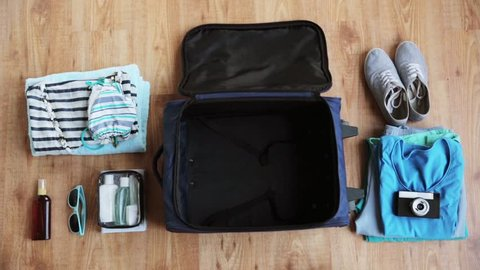 hands packing travel bag with personal stuff