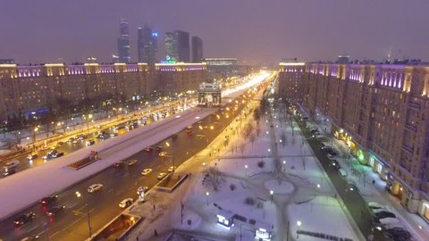 Kutuzovskiy prospect avenue Triumphal Arch holiday decoration. Night lights illumination. Aerial drone flight. Moscow Russia cowered in snow and ice. New year city road traffic. High altitude panorama