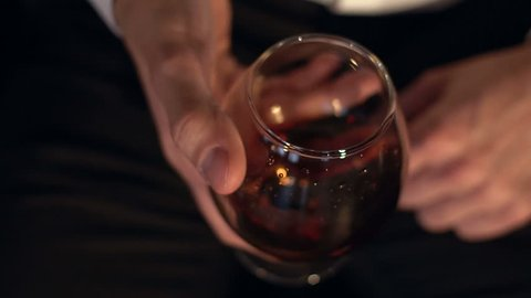 The glass with splashes cognac, slow motion. Glass of cognac in the man's hand.