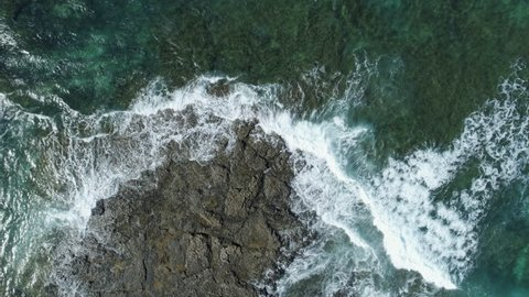 Slow motion shot of waves rushing towards rocky shore. Aerial drone footage of ocean waves washing up on rock at beach. The video is filmed from an overhead perspective.