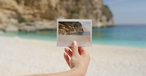 Close up hand holding polaroid photograph in front of beautiful tropical beach travel concept