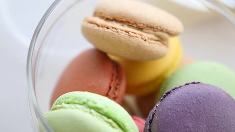 Close-up of colorful French macarons or macaroons, gourmet dessert closeup loop. Colorful macaroons on showcase in a fancy cafe.