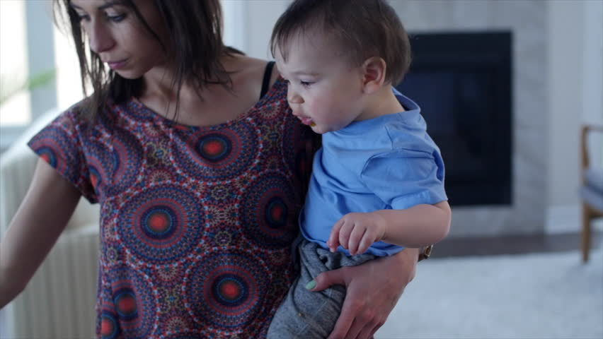 Stylish young mom feeds baby boy in her arms | Shutterstock HD Video #24214594