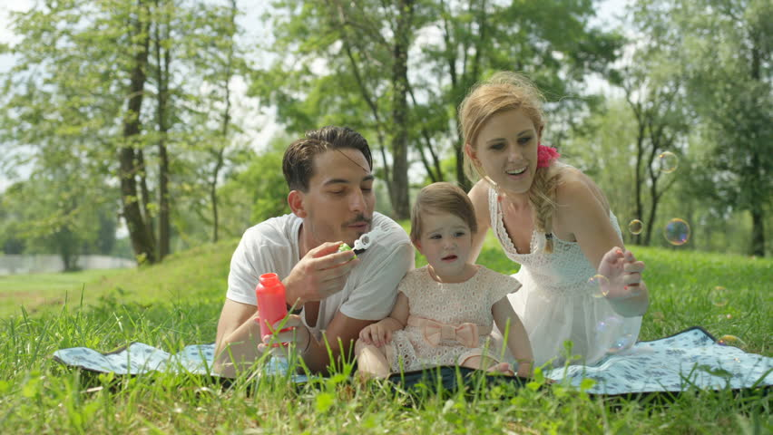 SLOW MOTION, CLOSE UP, DOF: Cute happy young family lying on blanket on the grass in local park on beautiful sunny spring day. Dad blowing bubbles, beautiful blonde mother playing with sweet baby girl